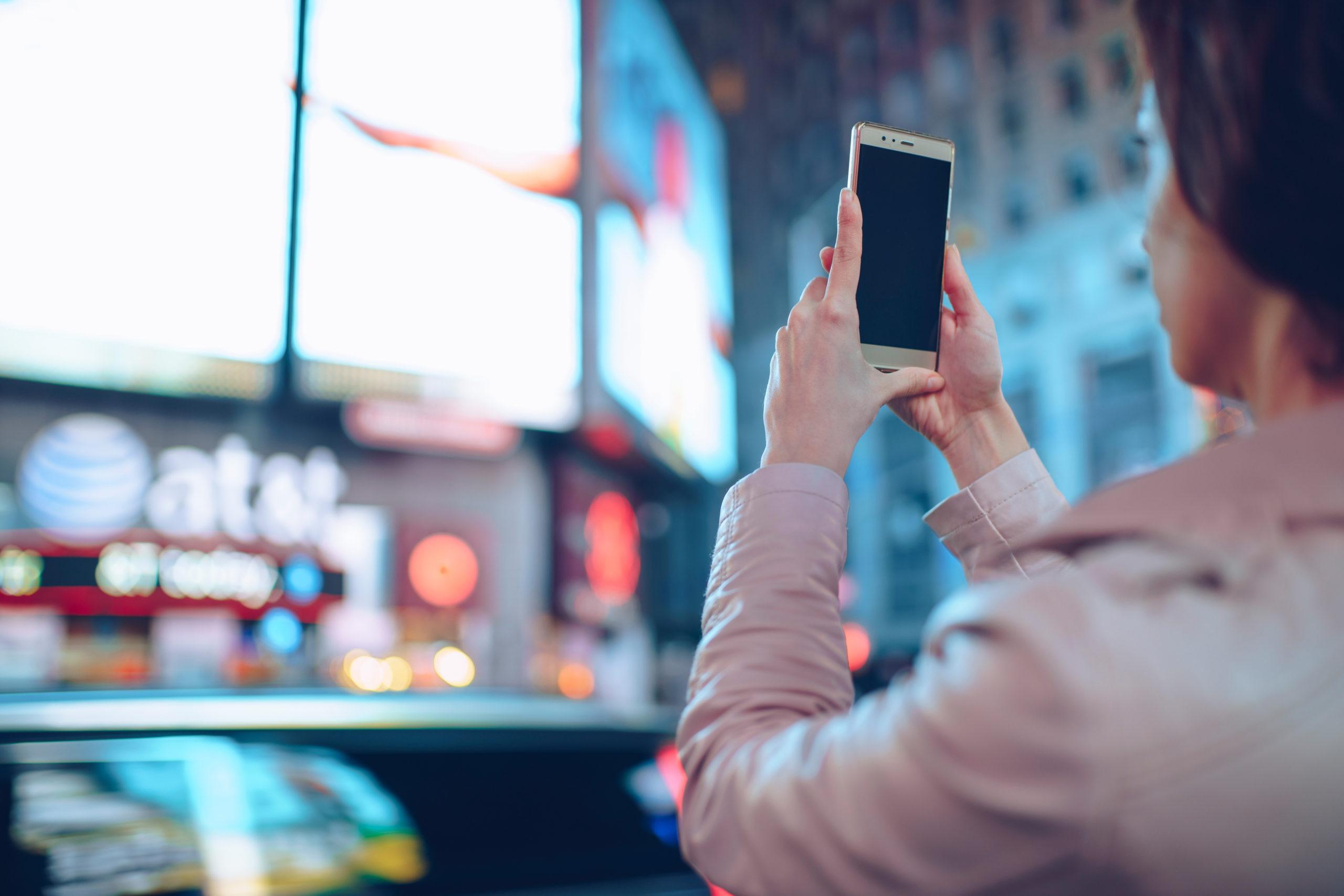 Chica sacando fotos a las vallas publicitarias de Times Square en Nueva York