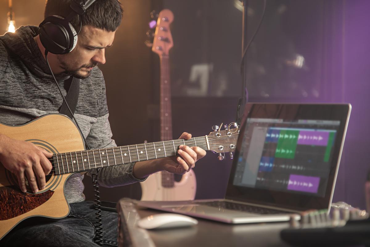 Guitarrista tocando la guitarra en el estudio de grabación.